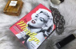 The little book of Marilyn, a little red book lies on a grey fur blanket with Chanel perfume and a diamond bracelet.
